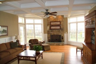 Living room with lots of glass, stone fireplace and coffered ceiling