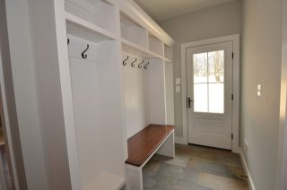 Contemporary Mudroom with custom built-ins and wood bench
