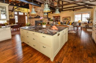 Soapstone kitchen island with green shaker cabinets