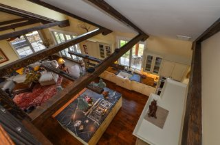 Arial view of kitchen and living area from walkway. Features wood beams