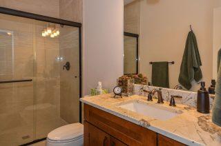 Granite counter, shaker cabinets, and walk in shower in modern farmhouse spare bath.
