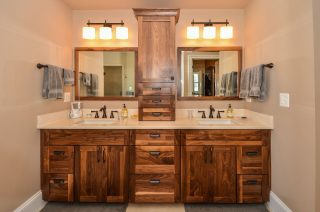Walnut cabinets and matching framed mirrors in modern farmhouse master bathroom.