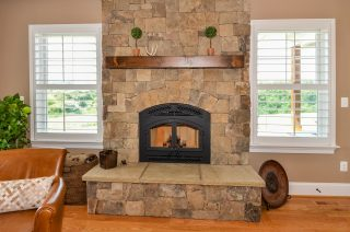 Fireplace with cut stone and wood mantle