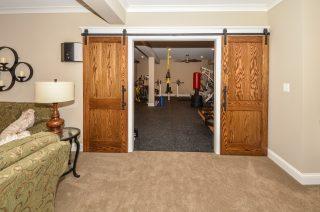 sliding barn doors reveal exercise room beyond