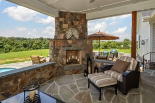 Outdoor Fireplace on modern farmhouse covered back patio